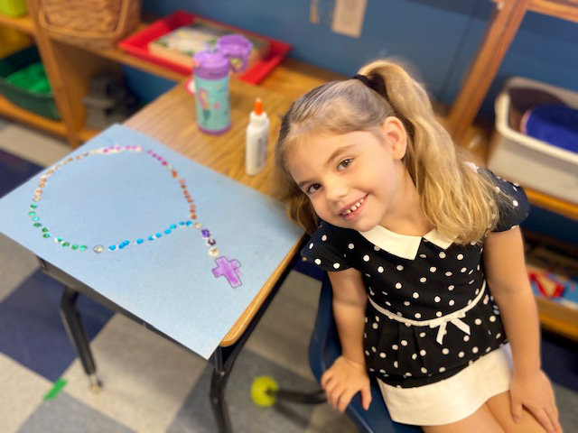 Student with rosary craft project